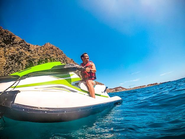Młody chłopak cieszyć się odrzutowcem wycieczkowym wycieczką sportem wodnym i uśmiechać się turystami bawić się niebieski ocean aktywny mężczyzna w letnie wakacje