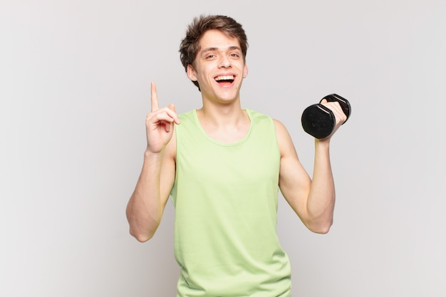 Młody chłopak czując się jak szczęśliwy i podekscytowany geniusz po zrealizowaniu pomysłu, radośnie unosząc palec, eureka!. koncepcja hantle