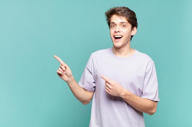 Młody chłopak czujący radość i zaskoczenie, uśmiechający się ze zszokowanym wyrazem twarzy i wskazujący na bok