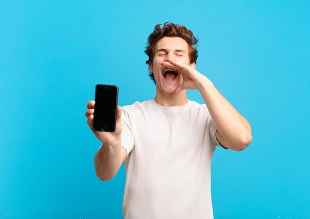 Młody chłopak czuje się szczęśliwy, podekscytowany i pozytywnie nastawiony, wydaje wielki okrzyk z rękami przy ustach, woła. koncepcja ekranu telefonu