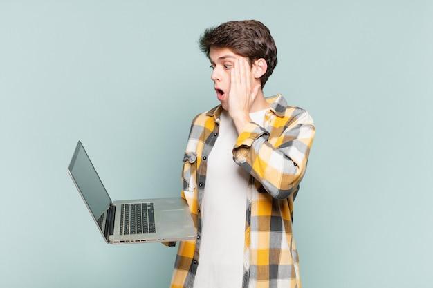 Młody chłopak czuje się szczęśliwy, podekscytowany i zaskoczony, patrząc w bok z obiema rękami na twarzy. koncepcja laptopa