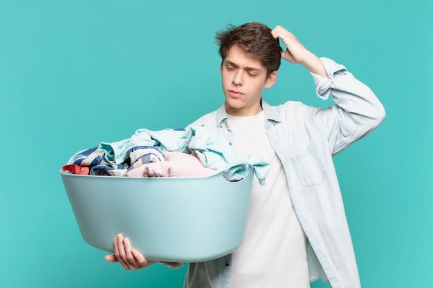 Młody chłopak czuje się zakłopotany i zdezorientowany, drapiąc się po głowie i patrząc w bok, piorąc ubrania