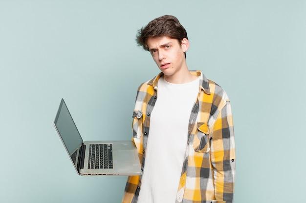 Młody chłopak czuje się zakłopotany i zdezorientowany, z tępym, oszołomionym wyrazem twarzy, patrzący na coś nieoczekiwanego. koncepcja laptopa