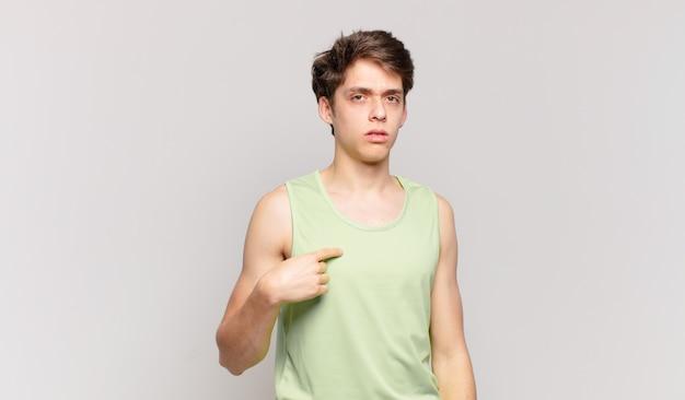 Młody chłopak czuje się zdezorientowany, zdezorientowany i niepewny, wskazując na siebie, zastanawiając się i pytając, kto, ja?