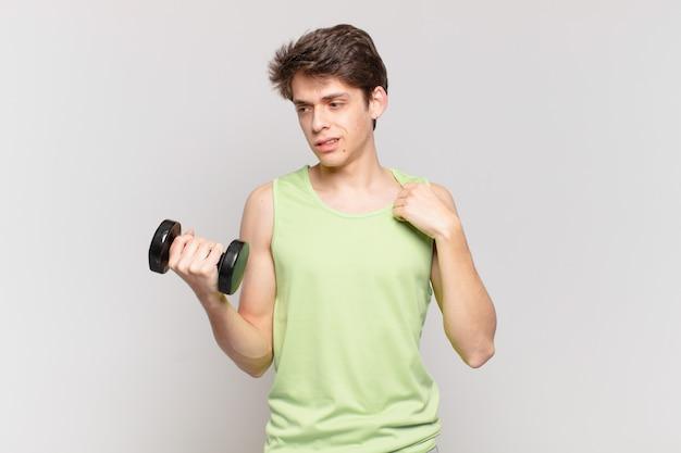 Młody chłopak czuje się zestresowany, niespokojny, zmęczony i sfrustrowany, ciągnie za koszulkę, wygląda na sfrustrowanego problemem