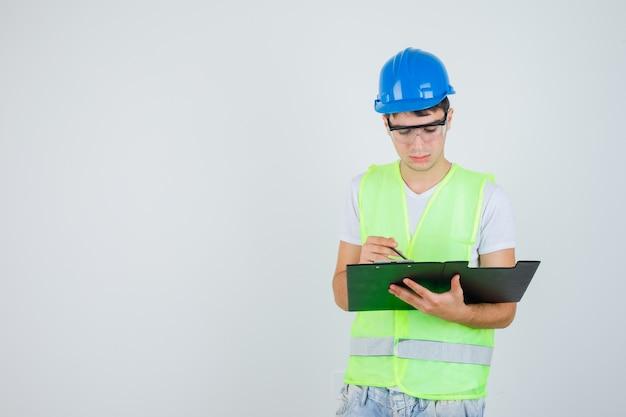Młody chłopak czytanie notatek w folderze plików, trzymając pióro w mundurze budowy i patrząc skoncentrowany, widok z przodu.