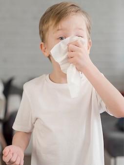 Młody chłopak dmuchanie nosa