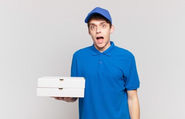 Młody chłopak dostarczający pizzę wygląda na bardzo zszokowanego lub zaskoczonego, gapi się z otwartymi ustami i mówi wow