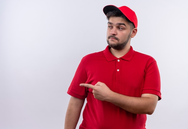 Młody chłopak dostawy w czerwonym mundurze i czapce patrząc na bok z wyrazem sceptyka, wskazując palcem wskazującym w bok