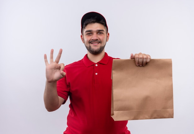 Młody chłopak dostawy w czerwonym mundurze i czapce, trzymając pakiet papieru uśmiechnięty przyjazny pokazując znak ok