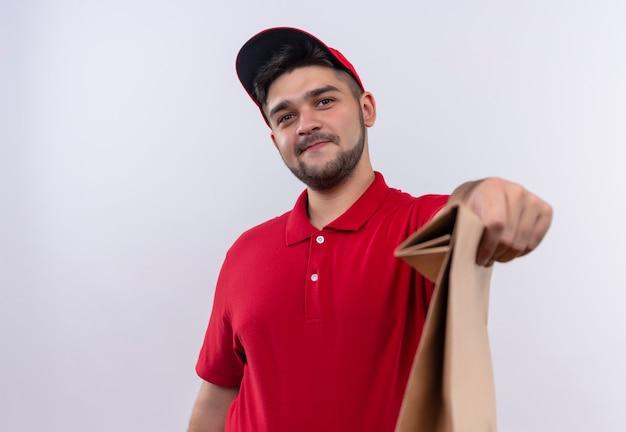 Młody chłopak dostawy w czerwonym mundurze i czapce trzymając papierowy pakiet uśmiechnięty przyjazny