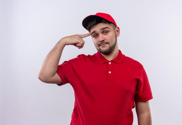 Młody chłopak dostawy w czerwonym mundurze i czapce wyglądający na pewnego siebie wskazującego na skroń skupiony na zadaniu