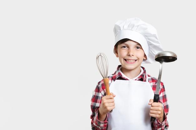 Młody chłopak gospodarstwa narzędzia do gotowania