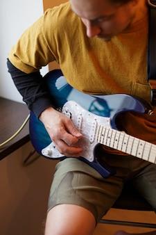 Młody chłopak gra na gitarze elektrycznej siedzącej przy oknie