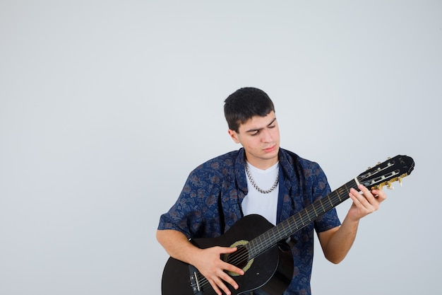 Młody chłopak gra na gitarze siedząc aganista w t-shirt i patrząc pewnie, z przodu.