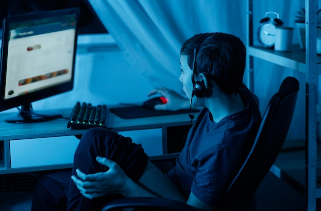 Młody chłopak gra na komputerze