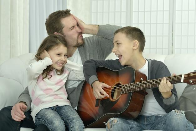 Młody chłopak grający na gitarze dla swojej rodziny