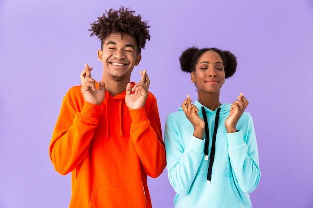 Młody chłopak i dziewczyna stojąc razem z skrzyżowanymi palcami, odizolowane na fioletowej ścianie