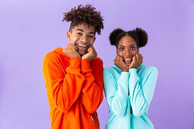 Młody chłopak i dziewczyna uśmiechając się i dotykając policzki, na białym tle nad fioletową ścianą