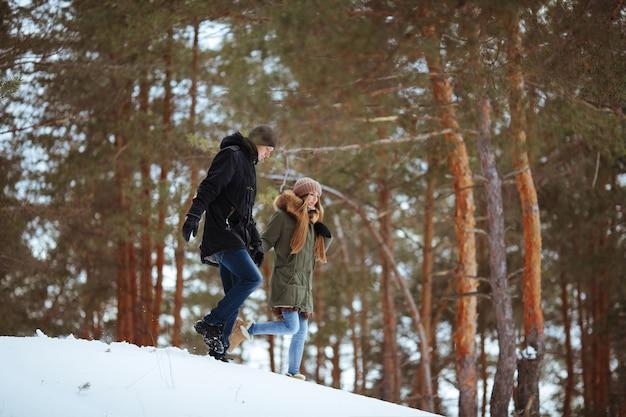 Młody chłopak i dziewczyna w zimowe ubrania, ciesząc się śniegiem w lesie