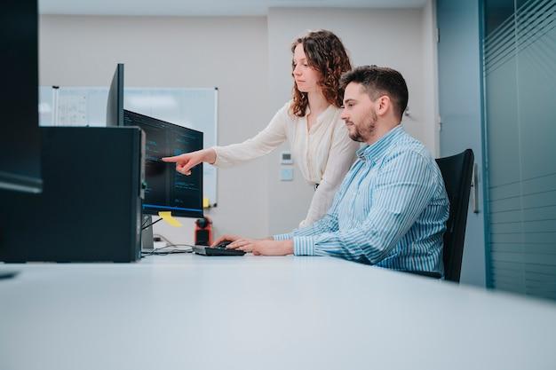 Młody chłopak i kobieta rasy kaukaskiej noszenie masek twarzy współpracowników w komputerze