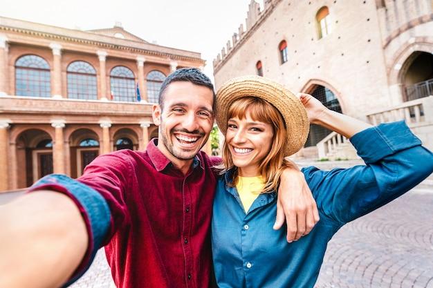Młody chłopak i zakochana dziewczyna bawią się, robiąc selfie na wycieczce po starym mieście