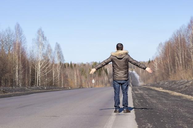 Młody chłopak idzie poboczem w kurtce. droga w lesie wczesną wiosną.