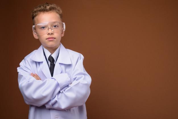Młody chłopak jako lekarz na brązowej ścianie