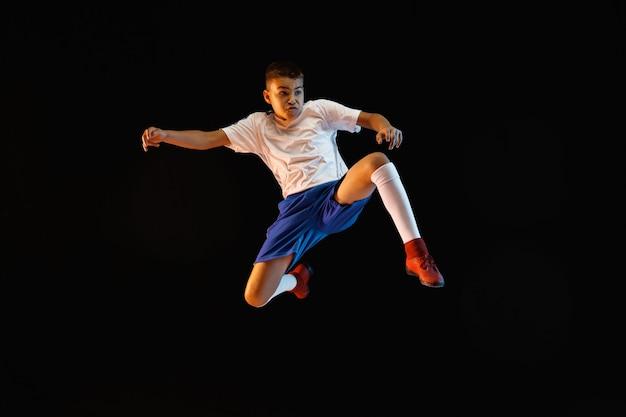 Młody chłopak jako piłkarz lub piłkarz na ciemnej ścianie