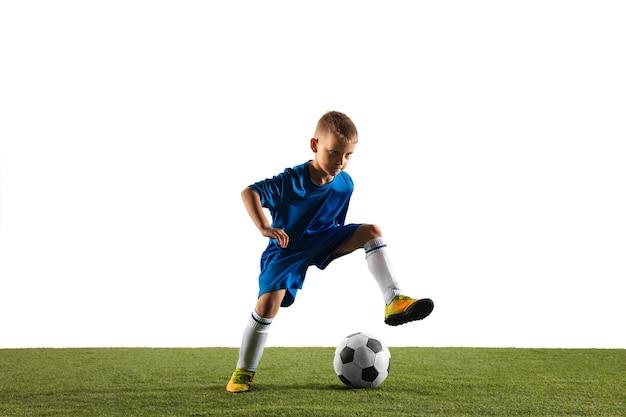 Młody chłopak jako piłkarz lub piłkarz w odzieży sportowej co zwód lub kopnięcie z piłką do bramki na tle białego studia. dopasuj grającego chłopca w akcji, ruchu, ruchu w grze.