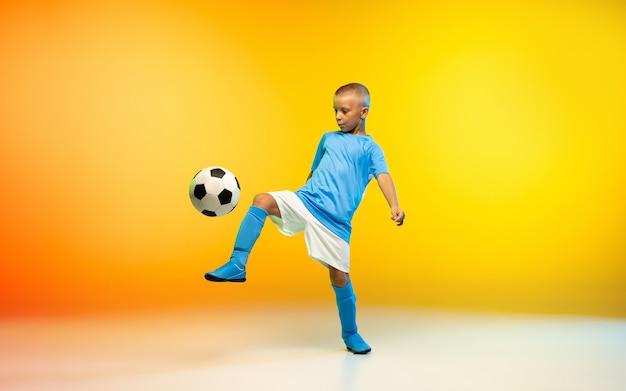 Młody chłopak jako piłkarz lub piłkarz w odzieży sportowej ćwiczący na gradientowym kolorze żółtym