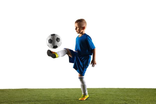 Młody chłopak jako piłkarz lub piłkarz w odzieży sportowej, wykonując zwód lub kopnięcie piłką do bramki na białym tle.