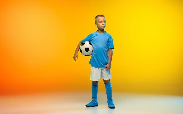 Młody chłopak jako piłkarz w stroju sportowym odizolowany na gradientowym żółtym w neonowym kolorze