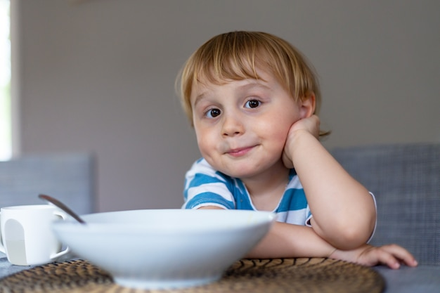 Młody chłopak jedzenie włoskiego makaronu w domu. małe dziecko korzystających z posiłku spaghetti w pomieszczeniu