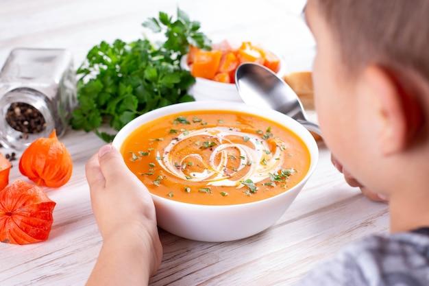 Młody chłopak jedzenie zupy dyniowej. pojęcie żywności dla niemowląt.