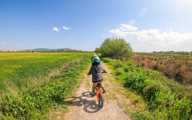 Młody chłopak jedzie na swoim rowerze pedał z kaskiem na wsi