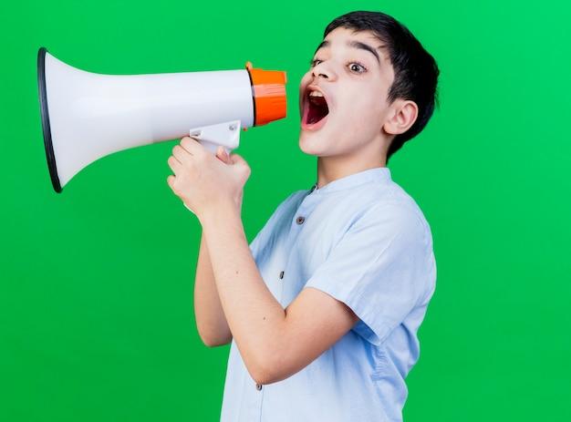 Młody chłopak kaukaski stojący w widoku profilu rozmawia przez głośnik na białym tle na zielonym tle z miejsca na kopię