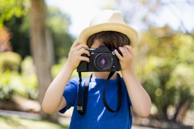 Młody chłopak klikając zdjęcie z aparatu