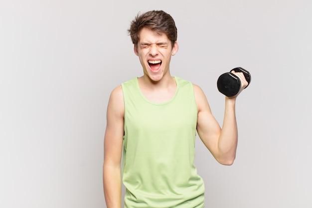 """Młody chłopak krzyczy agresywnie, wygląda na bardzo rozgniewanego, sfrustrowanego, oburzonego lub zirytowanego, krzyczy """"nie"""". koncepcja hantle"""
