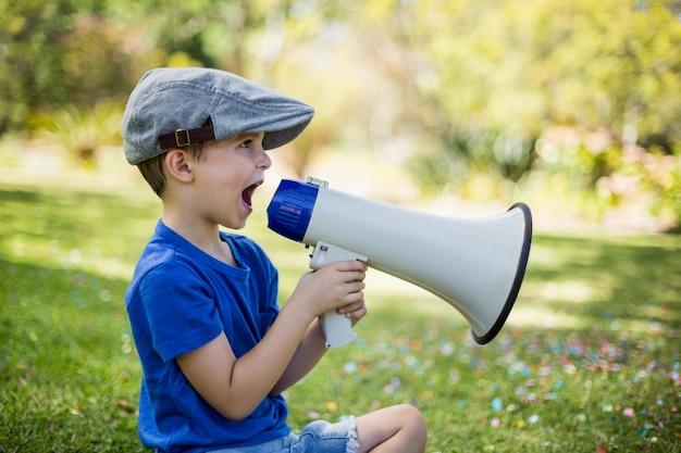 Młody chłopak mówi na megafon