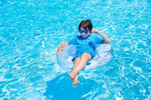 Młody chłopak na dmuchanym ringu w basenie latem.