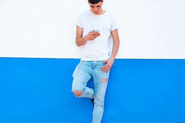 Młody chłopak na ścianie za pomocą smartfona