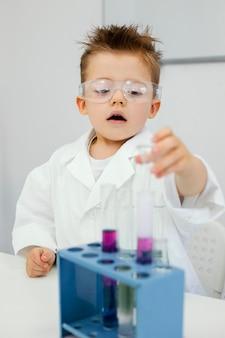 Młody chłopak naukowiec z okularami ochronnymi robi eksperymenty w laboratorium