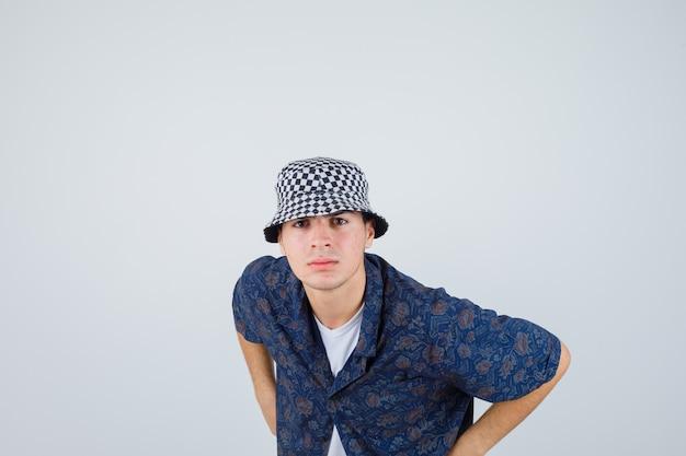 Młody chłopak patrząc na kamery, pozując w białej koszulce, kwiecistej koszuli, czapce i patrząc poważnie. przedni widok.
