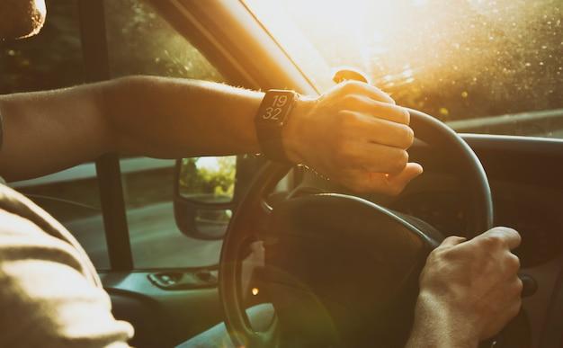 Młody chłopak patrząc na swoje smartwatche na dłoni siedzący w nowoczesnym samochodzie