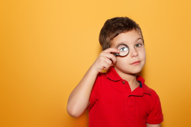Młody chłopak patrząc przez lupę na żółtym tle. miejsce na tekst