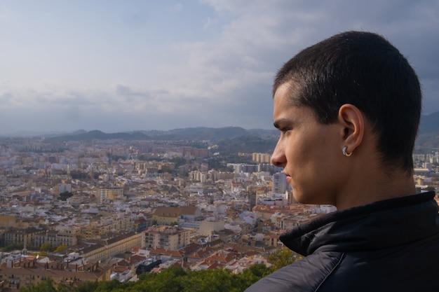 Młody chłopak patrząc z boku na miasto malaga w hiszpanii.