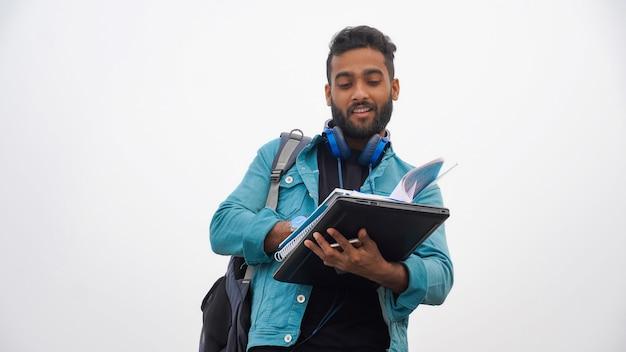 Młody chłopak pisze w notesie na białym tle