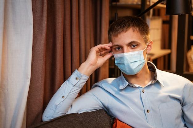 Młody chłopak pochodzenia kaukaskiego w koszuli i masce ochronnej siedzi sam na kanapie w domu ...