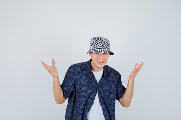 Młody chłopak podnosząc ręce z radości w białej koszulce, kwiecistej koszuli, czapce i patrząc szczęśliwy, widok z przodu.